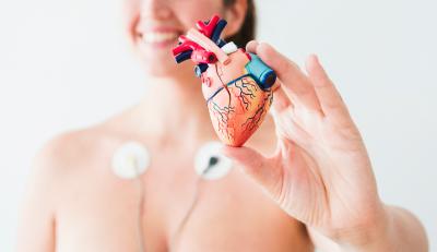 paciente com eletrodos no peito para realização de eletrocardiograma e segurando uma maquete de coração