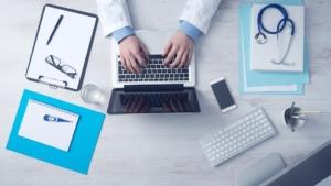 mãos de um médico sobre um teclado de notebook ao lado de um estetoscópio e pranchetas