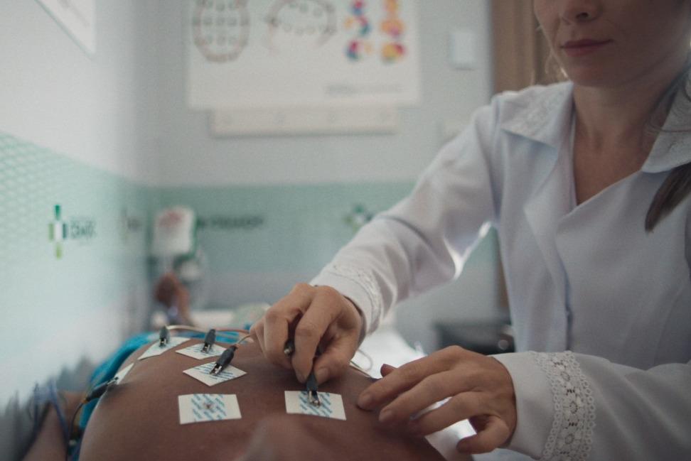 Enfermeira realizando exame de eletrocardiograma em paciente