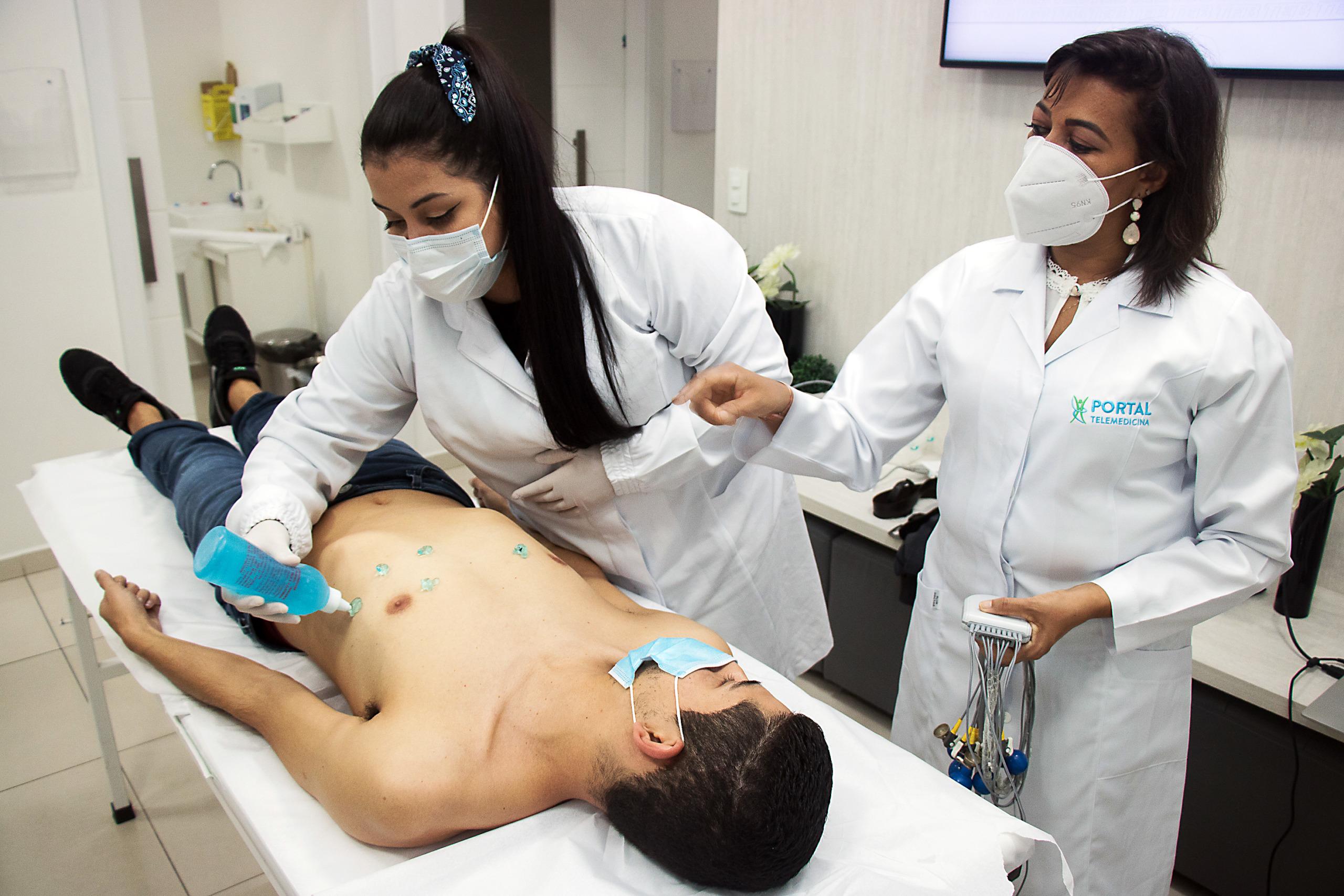enfermeiras aplicando gel na pele de paciente para colocação de eletrodos e realização de um exame de eletrocardiograma